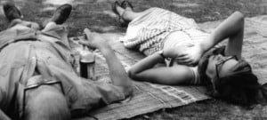 Le Corbusier and Jane Drew lying on a rug, relaxing in a garden
